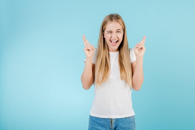 Happy young girl with fingers crossed hoping and praying for luck isolated over blue