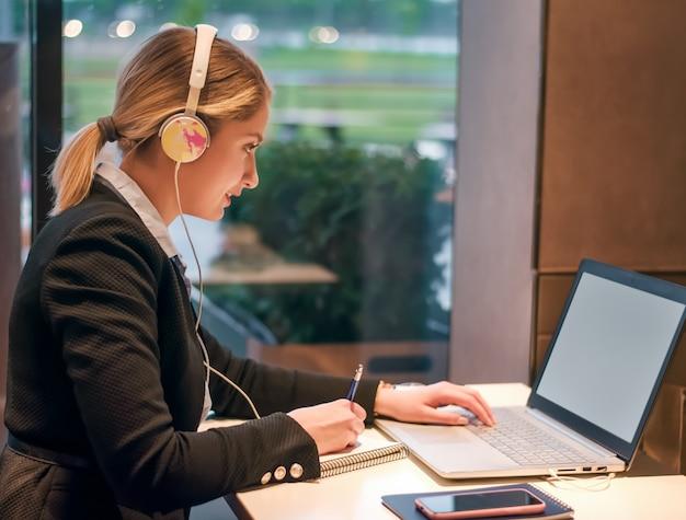 Счастливая молодая девушка с наушниками смотрит на экран ноутбука и улыбается, читает онлайн-курсы, учится или работает удаленно