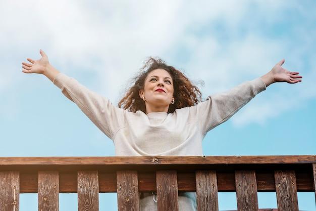 행복 한 어린 소녀, 그녀의 팔을 제기, 백그라운드에서 하늘을 올려. 행복, 축하 및 양성 개념.