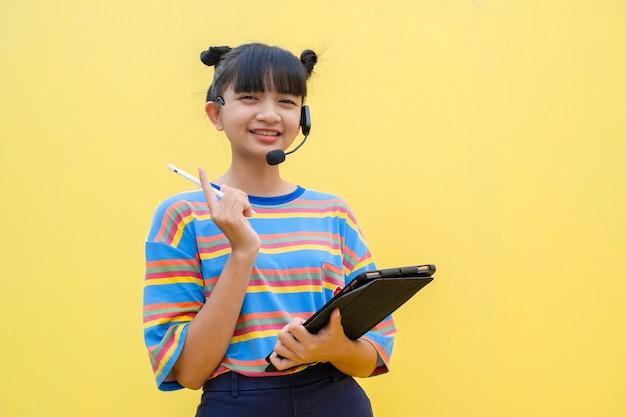 노란색 바탕에 노트북을 들고 있는 행복한 어린 소녀아시아 소녀