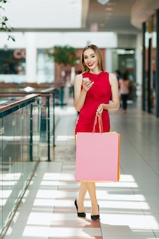 Счастливая молодая девушка с светло-каштановыми волосами и красными губами, стоящая с красочными хозяйственными сумками, держа мобильный телефон, концепцию покупок, портрет.