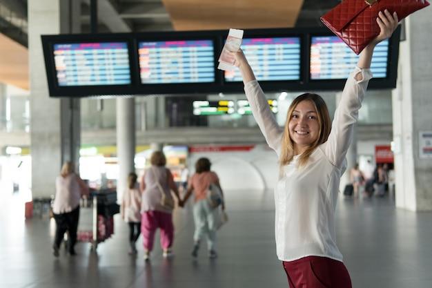 여권과 티켓을 들고 있는 행복한 어린 소녀는 안내판과 함께 점수판 배경에 손을 들었다