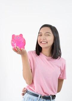 흰색 바탕에 돼지 저금통과 행복 한 어린 소녀.