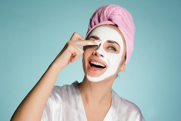 顔に白い保湿マスクを適用する頭にピンクのタオルで幸せな少女