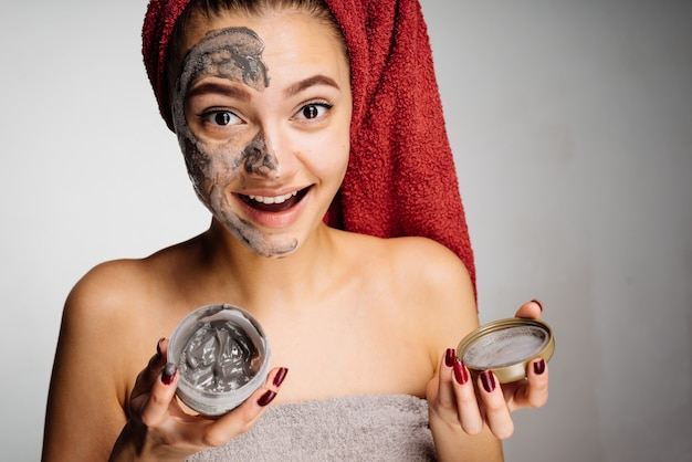 Happy young girl with a red towel on her head applied a useful clay mask to half the face, laughs
