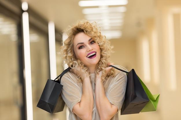 쇼핑몰에서 쇼핑백을 들고 웃고 있는 행복한 어린 소녀
