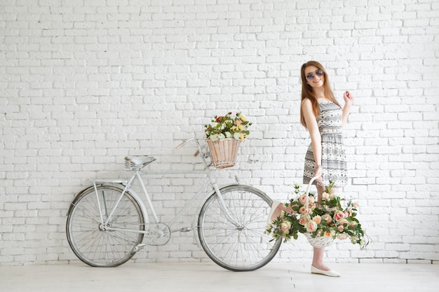 Happy young girl with vintage bicycle and flowers