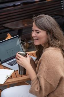 Счастливая молодая девушка, работающая в кафе с ноутбуком