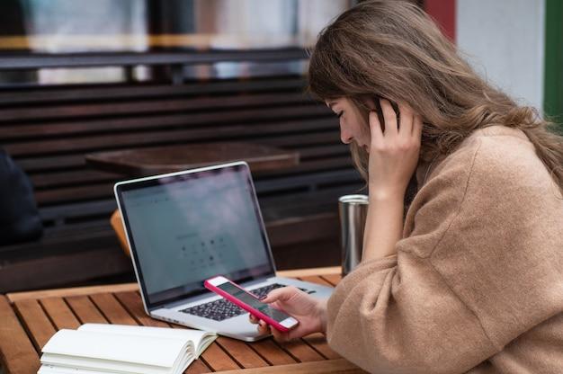 ノートパソコンでコーヒーショップで働いて幸せな若い女の子