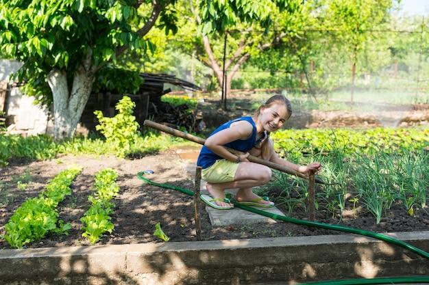 菜園の植物を除草するためにかがんで庭で働いて、笑顔で見上げる幸せな少女