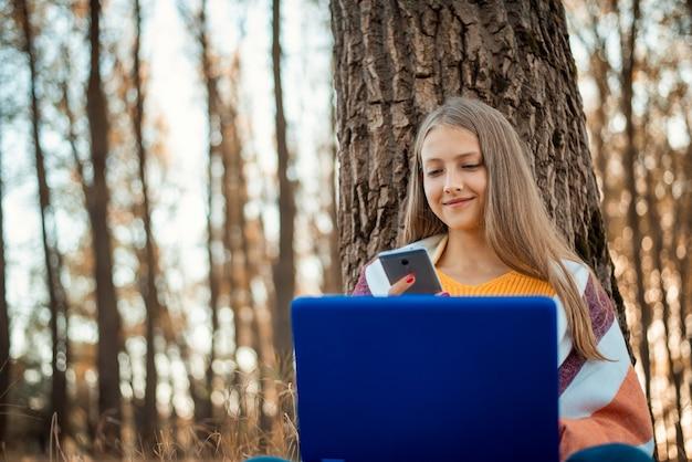 가을 공원에서 노트북과 휴대폰 작업을 하는 행복한 어린 소녀