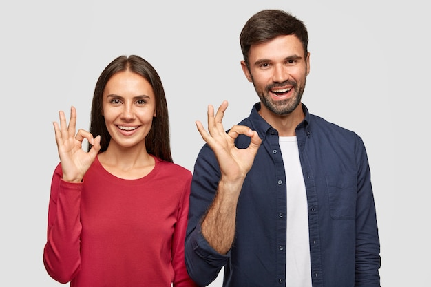 Happy young girlfriend and boyfriend show ok sign with hands, express excellent symbol, demonstrate their approval or agreement, have cheerful expressions, stand indoor against white wall
