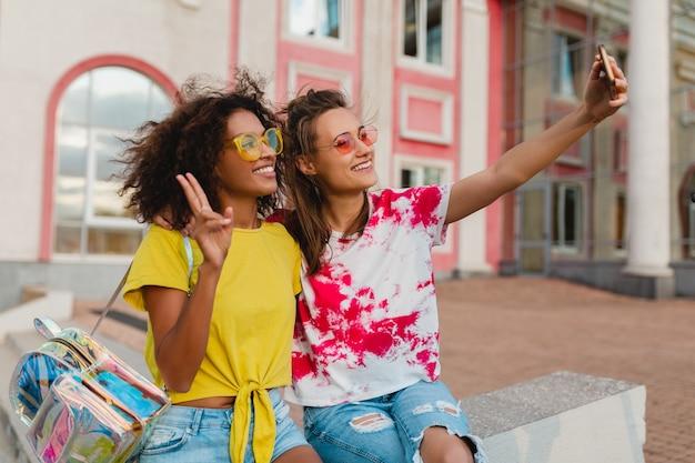 Счастливые молодые девушки друзья улыбаются, сидя на улице, принимая селфи фото на мобильный телефон, женщины веселятся вместе