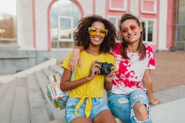 Счастливые молодые девушки друзья улыбаются, сидя на улице с фотоаппаратом, женщины веселятся вместе