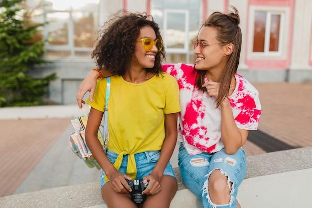 写真カメラで通りに座って笑っている幸せな若い女の子の友達、一緒に楽しんでいる女性