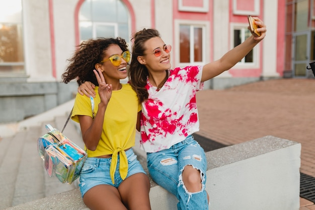 Happy young girls friends smiling sitting in street taking selfie photo on mobile phone, women having fun together