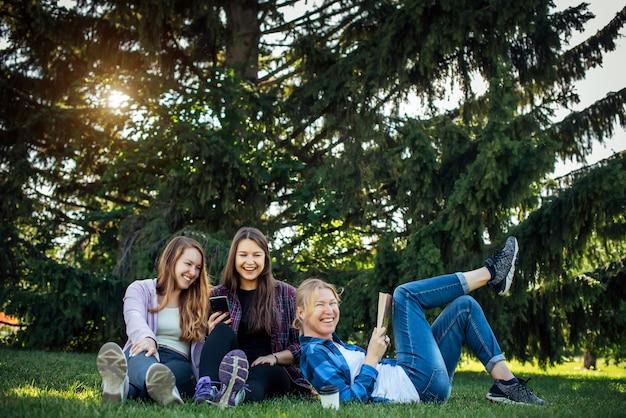 幸せな若い女の子は公園の緑の芝生に座って笑って楽しんでいます。金髪、ブルネット、赤毛の女の子がコミュニケーションを取り、スマートフォンを見てください。