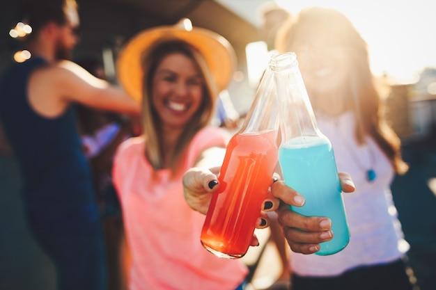Счастливые молодые девушки вместе веселятся на вечеринке на крыше