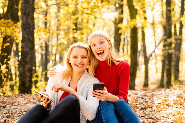 Happy young girls holding mobile phone and sitting on fallen leaves outdoor young women in autumn st...