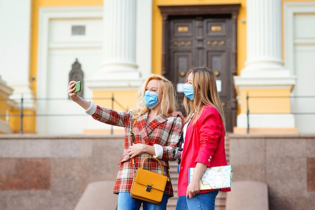 Happy young girls taking selfies in city.