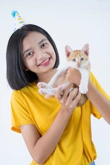 幸せな若い女の子服の黄色いシャツと猫とパーティーハット