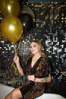 パーティーで輝く壁のそばに座っているシャンパンのフルートと風船の束を持つ幸せな若い魅力的な女性