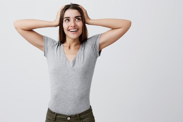 Счастливая молодая симпатичная кавказская девушка с темными длинными волосами в серой повседневной рубашке и джинсах улыбается, держась за руки на голову, смотрит в сторону со счастливым и взволнованным выражением лица