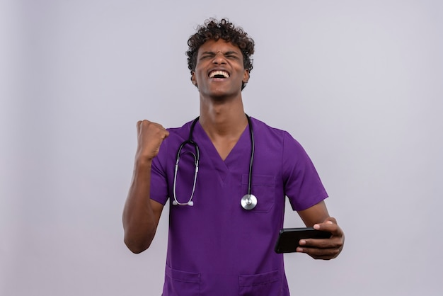 スマートフォンを握りこぶしで握りしめているバイオレットの医者の制服を着た巻き毛の幸せな若いハンサムな浅黒い肌の男
