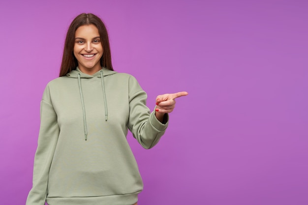 Happy young green-eyed brunette woman with natural makeup smiling widely whille showing aside with raised hand, being in nice mood while posing over purple wall