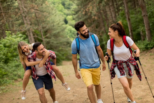 Happy young group hiking together through the forest