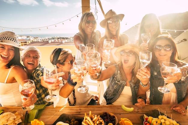 幸せな若者。人々のグループは一緒に楽しんで、家で屋外のグラスや飲み物でたくさんの賞賛を祝います-女性の友人のためのパーティーレジャー活動は楽しんで笑顔です-陽気な白人の女性