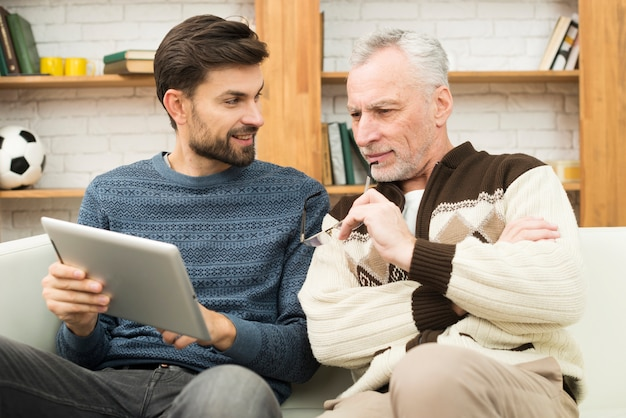 Happy young guy and aged man using tablet on settee