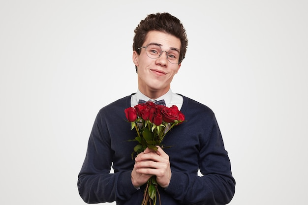 Happy young guy in elegant wear and glasses with bouquet of red roses in hands smiling and looking