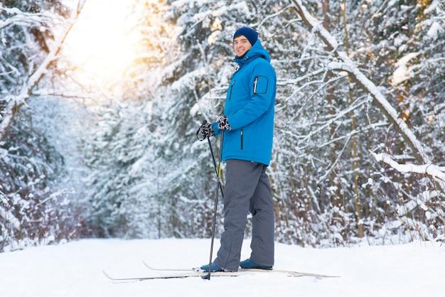 幸せな若い男は森の中でクロスカントリースキーに行きます。男性は健康的なライフスタイルを送り、ウィンタースポーツに従事しています。