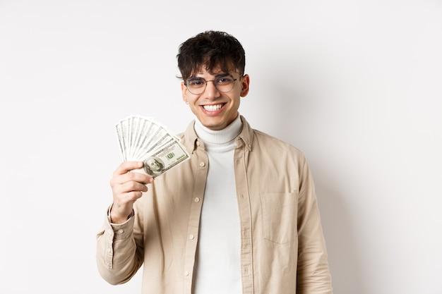 ドル札を持って笑顔でお金を稼ぎ、カメラの代役を元気に見ている幸せな若い男...