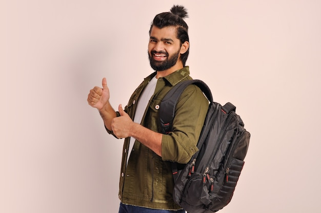 Счастливый молодой парень показывает большие пальцы руки обеими руками, держа рюкзак