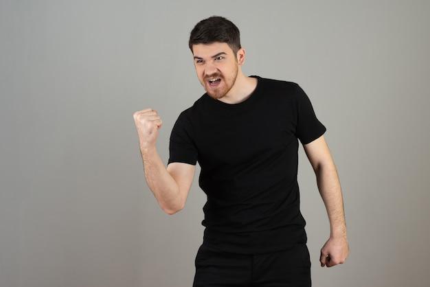 幸せな若い男は彼の拳を握りしめ、何かを祝います。