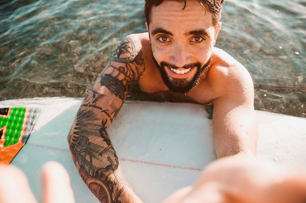 Happy young guy taking selfie and lying on surf board in water