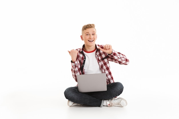 Happy young guy using laptop computer pointing to copyspace.