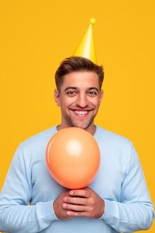 Счастливый молодой парень с воздушным шаром празднует праздник