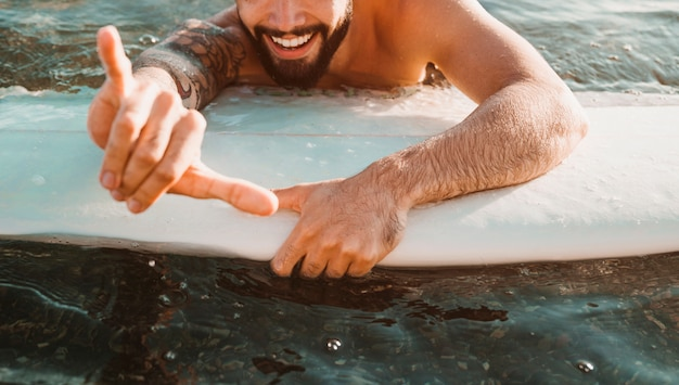 Happy young guy with shaka gesture lying on surf board in water