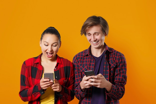 Happy young guy and woman with smartphones in hand, chatting with each other and laughing. colored orange wall