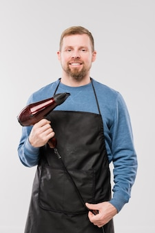Happy young hairdresser in apron and blue pullover holding hairdryer while working in front of camera
