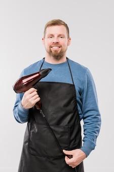 カメラの前で作業しながらヘアドライヤーを保持しているエプロンと青いプルオーバーで幸せな若い美容師