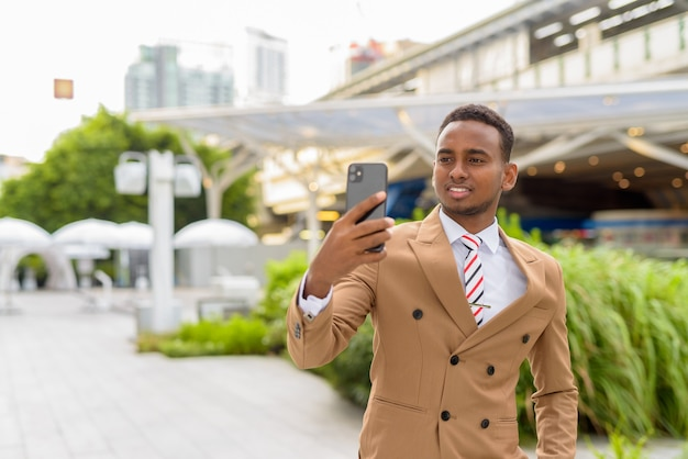 Счастливый молодой красивый африканский бизнесмен, делающий селфи в городе