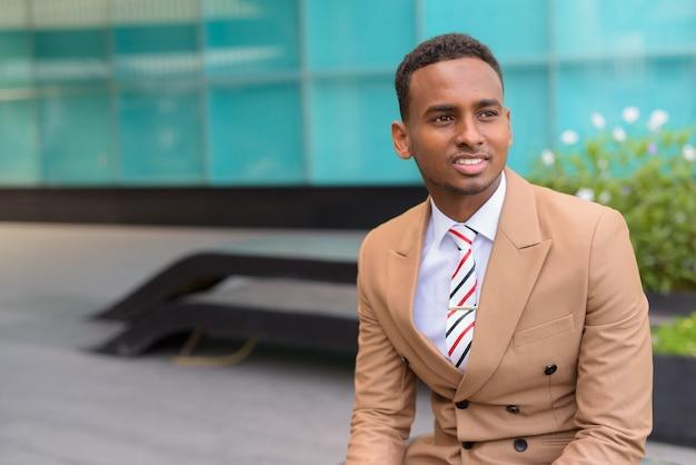 幸せな若いハンサムなアフリカの実業家思考と屋外の都市に座っています。