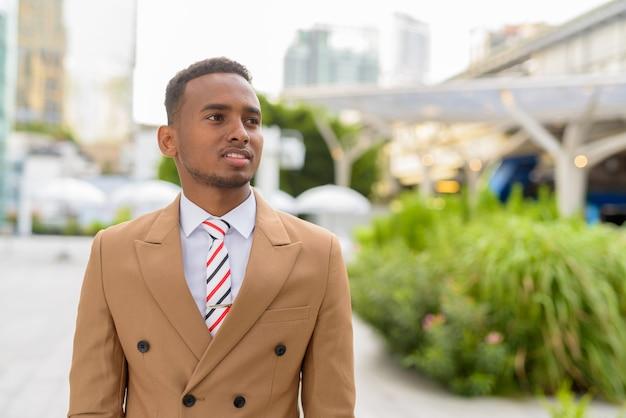 屋外の街で考えて幸せな若いハンサムなアフリカの実業家