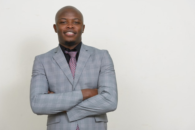 Happy young handsome bald african businessman smiling with arms crossed