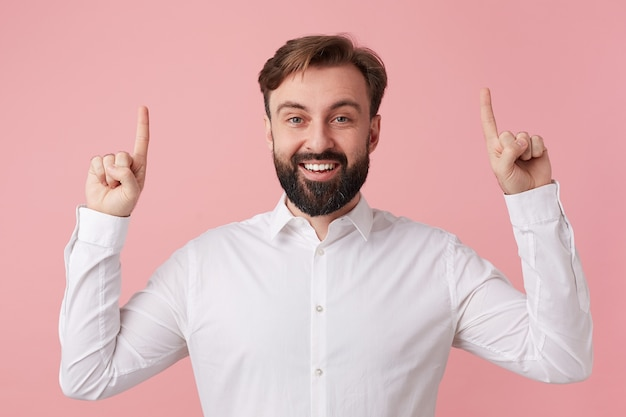 Happy young handsome bearded man, wearing a white shirt. wants to tell cool news. looking at the camera and broadly smiling, points fingers up on copy space isolated over pink background.
