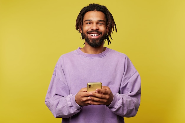 Happy young handsome brown haired man with dreadlocks smiling cheerfully at camera while holding mobile phone, dressed in purple sweatshirt while being isolated over yellow background